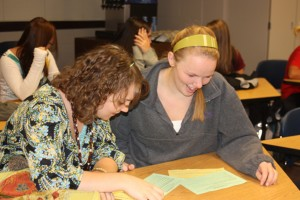 Ashley Anderson and Caitlin Theisen look over information about Students Stepping Up